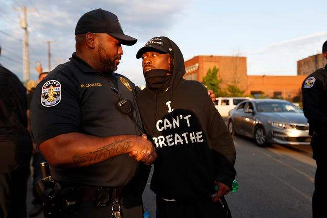 Chris Buntin, right, shakes hands with LMPD Sgt. Michael Jackson. Jackson walked with the crowd from downtown to 26th and Broadway. Buntin said he thought that showed a lot of respect, that Jackson cared about the situation.