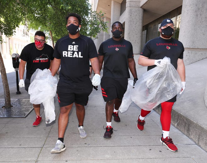 (R-L) U of L football players Cole Bentley, Adonis Boone, Caleb Chandler and Emmanual Sowders joined a group volunteers during a community cleanup through downtown Louisville, Ky. on June 2, 2020.  The group, a combination of the Jamon Brown Foundation and the Metro United Way, was showing its support of the right to protest while advocating that it remains peaceful following the police shootings of Breonna Taylor and David McAtee.