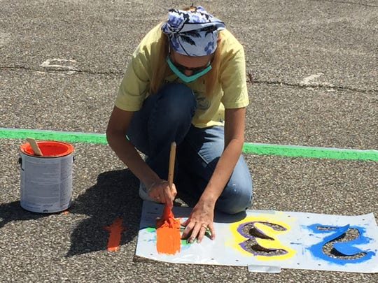 Heather Richmond paints numbers on a four square game at Springmill STEM Elementary School on Monday afternoon.