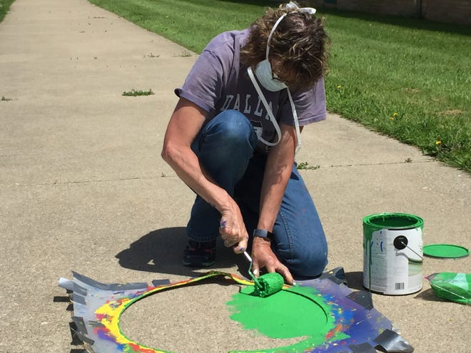 Diana Flannigan paints a green circle Monday afternoon at Springmill STEM Elementary School.