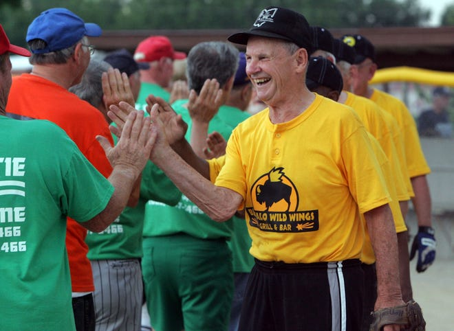 Players line up to shake hands after a Marion Senior Softball Association game in 2012. The three leagues the association organizes will be playing this summer despite the coronavirus pandemic, starting June 15.