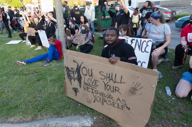 A group of people peacefully protest outside the Milwaukee District 5 Police Station on Monday.