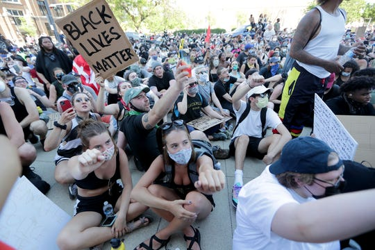 Protesters sit at the Milwaukee Police Department District 1 during a peaceful protest march in Milwaukee against the killing of George Floyd, an African American, by a white Minneapolis police officer.