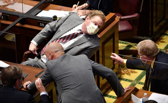 Rep. Bill Beck leans into a conversation with other legislators as the Tennessee House of Representatives began their session this week in Nashville, Tenn. Tuesday, June 2, 2020 Barriers were put between desks and many of the lawmakers were wearing masks.