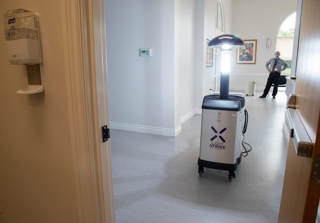 Matthew Crilow, the general manager for environmental services at NCH downtown, steps back while a Xenex robot cleans a reception area at the Neighborhood Health Clinic in Naples on Tuesday, June 2, 2020.