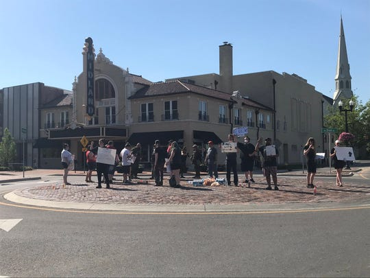 About 25 people stand on a downtown roundabout as part of a protest against racism early evening on June 2, 2020.