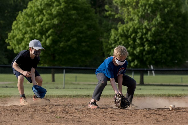 Chance Hedger catches a grounder while teammate Parker Cook backs him up during a Granville Recreation District Farm Division practice this year at Raccoon Valley Park. The boys were a handful of kids and coaches wearing face masks during the team's first practice of the season.