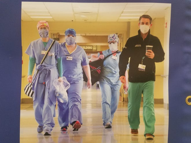 """This picture appeared in the Kings County Hospital (New York City) online magazine, and was featured on a poster inside the hospital. It was captioned """"The cavalry has arrived,"""" and shows CRNAs (from left) Samantha Dawson of Tullahoma, Tennessee, Beth Tuma of Granville and Charlotte Wight from Nashville, Tennessee, being escorted by Dr. Andrew Winer to their assignment in the COVID-19 ICU on their first day in mid-April."""
