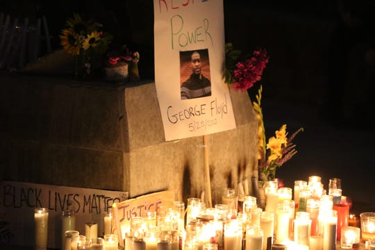 Candles burn late into the night at a memorial to George Floyd in Las Cruces, New Mexico, Monday June 1, 2020.