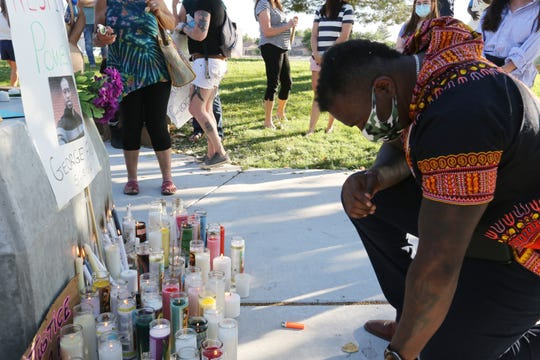 Doña Ana County Sheriff's Deputy Jamar Cotton kneels before a memorial during vigil held for George Floyd at Albert Johnson Park, Monday June 1, 2020. Floyd was killed a week ago in Minneapolis after a police officer knelt on his neck for almost nine minutes.