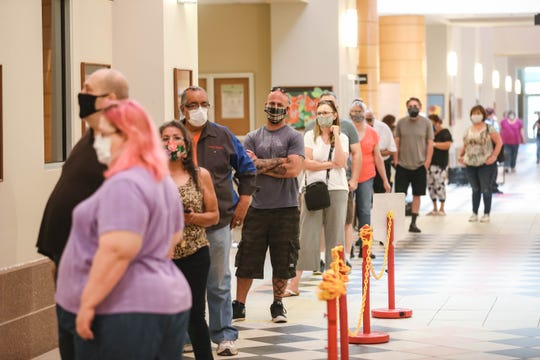 A line of waiting voters stretches down the hall at the Doña Ana County Government Center in Las Cruces on Tuesday, June 2, 2020.