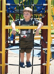 "Trent Duncan, 5, pauses on the playground structure at Livonia's Rotary Park on June 2, 2020 - which had recently reopened for residents. Trent was there with his mother Breigh who said: ""reopening the playgrounds helps a mother's sanity."""