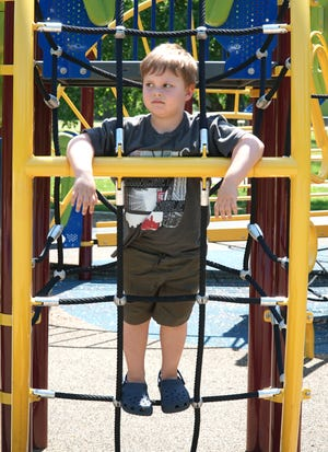 Trent Duncan, 5, pauses during a climb on the playground structure at Livonia's Rotary Park on June 2, 2020, shortly after the park reopened to residents. Trent was there with mom Breigh.