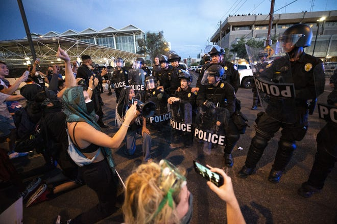 Three Phoenix police officers take a knee after protesters said they would go home if any officer would take a knee with them on June 1, 2020, in Phoenix. The protesters honored their word and peacefully left the area. Kneeling in front of the officers is protester Reshauna Striggles.