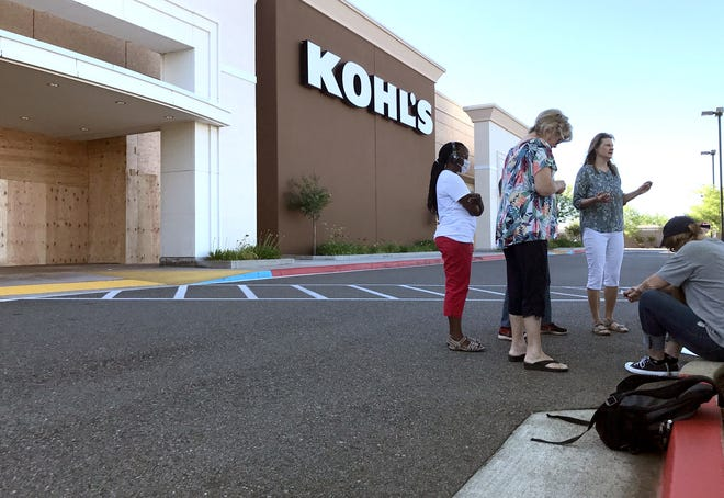 Several people participated in a prayer circle Tuesday morning, June 2, 2020, in front of the boarded-up Kohl's ahead of an evening march over the killing of George Floyd.