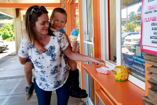 Corey Wright carries her son Isaiah Wright, 5, after they picked up their ice cream cones at On Any Sundae in Salem, Oregon, on Monday, June 1, 2020.