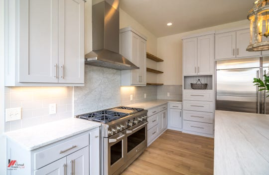 The kitchen features a six-burner range with marble countertops and a limestone island.