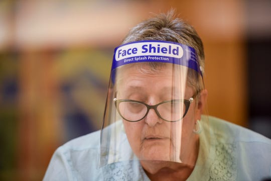 Kay Nelson wears a face shield as she works during the elections on Tuesday, June 2, 2020 in Sioux Falls, S.D.