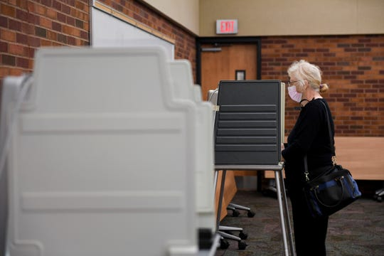 A voter wears a face mask as they cast their vote during the elections on Tuesday, June 2, 2020 in Sioux Falls, S.D.