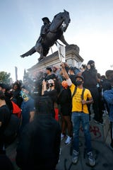 People gather nears the J.E.B. Stuart monument during a rally and march through the streets of Richmond, Va., Monday.