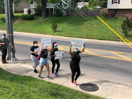 People held signs and wore face masks as they participated in a silent march through Staunton on June 2, 2020.