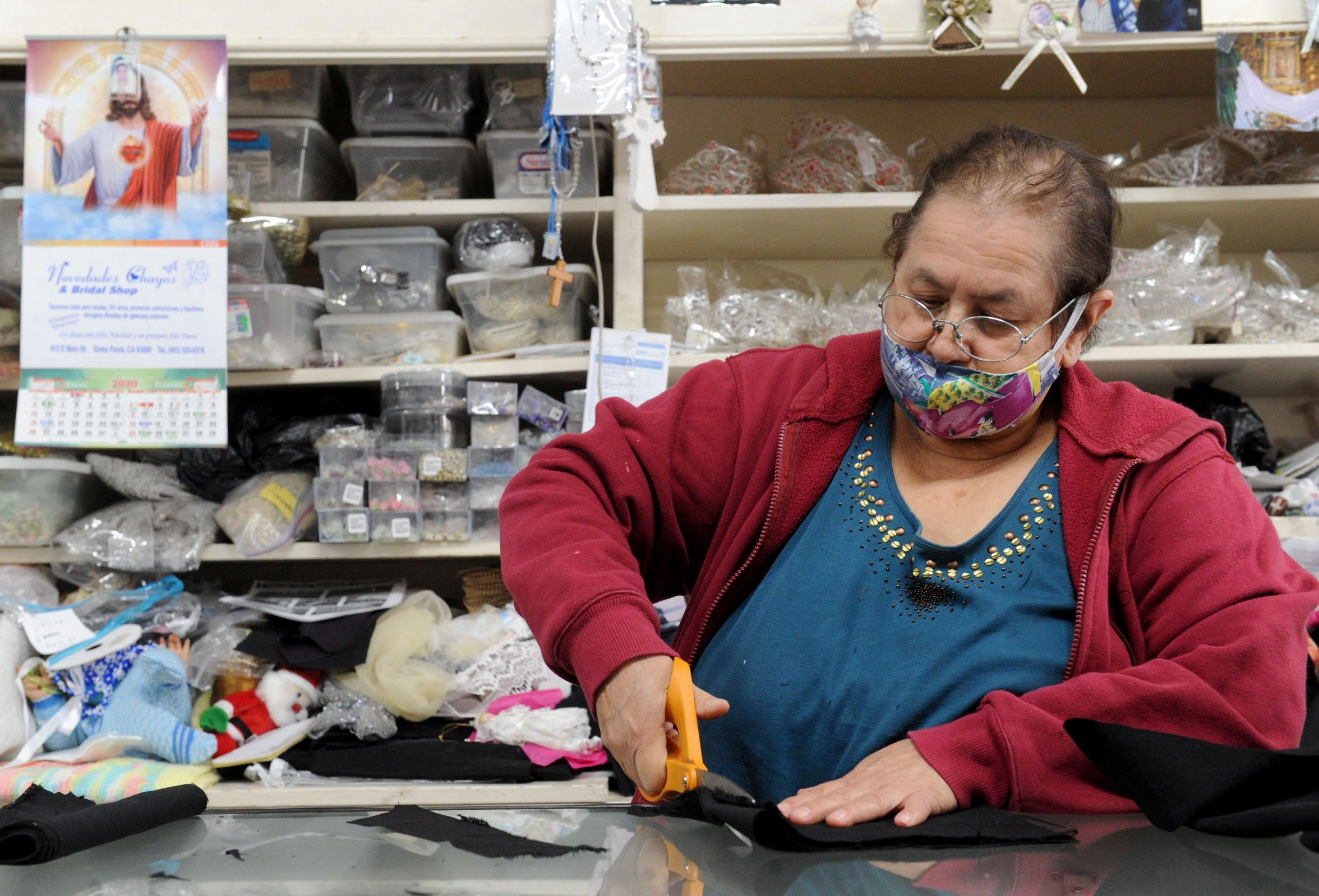 Cesaria Marin, owner of Novedades Chaos & Bridal shop in downtown Santa Paula, cuts cloth to make mask to sell on Tuesday, June 2, 2020. Business has been slow due to the coronavirus shutdown.