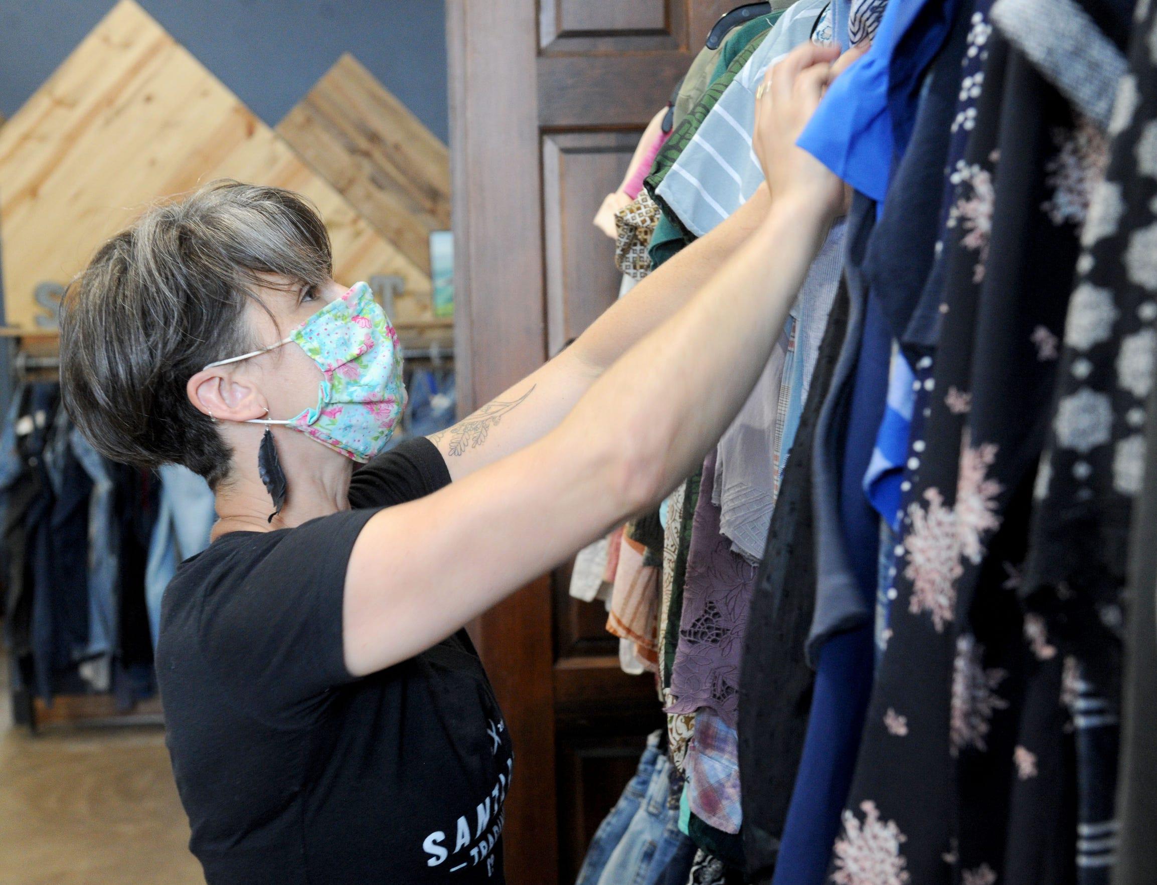 Tracy Hanna, owner of Santa Paula Trading Co in Santa Paula, rearranges clothes on Tuesday, June 2, 2020.
