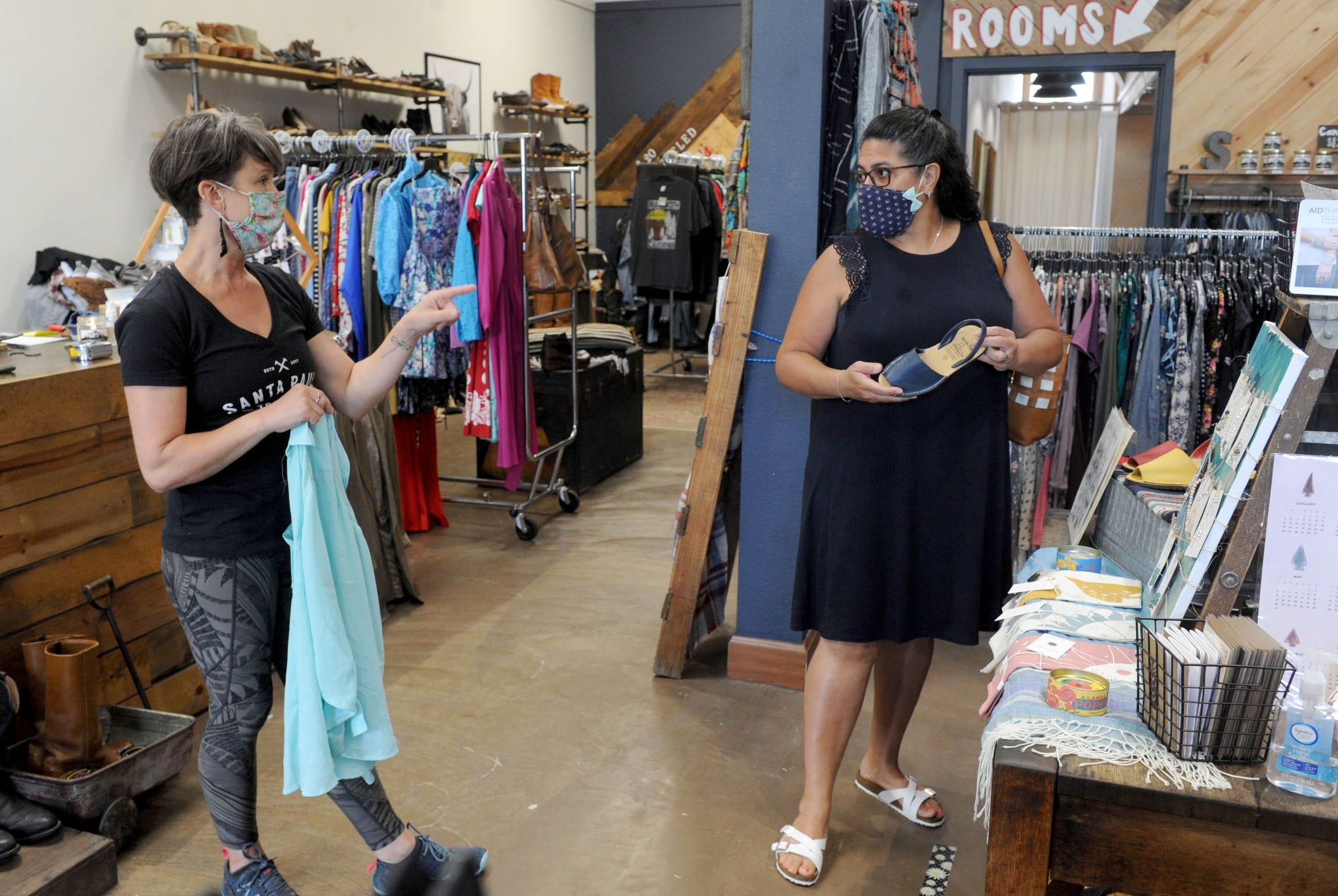 Tracy Hanna, left, owner of Santa Paula Trading Co in Santa Paula helps Yvette Enriquez, of Santa Clarita, on Tuesday, June 2, 2020.
