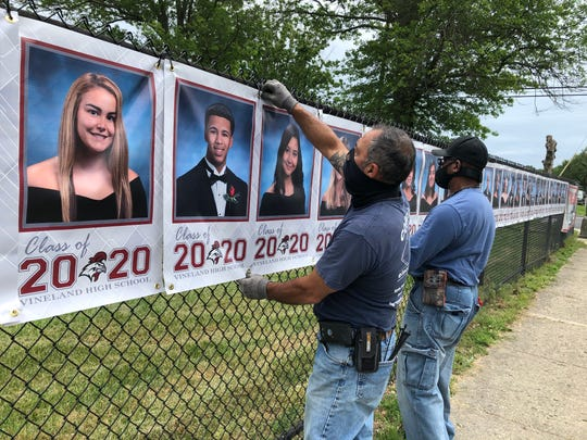 Vineland Public Schools staffers Joe Calderone (left) and Haywood Fonville add Class of 2020 banners to a pop-up exhibit on the Vineland High School campus. June 2, 2020