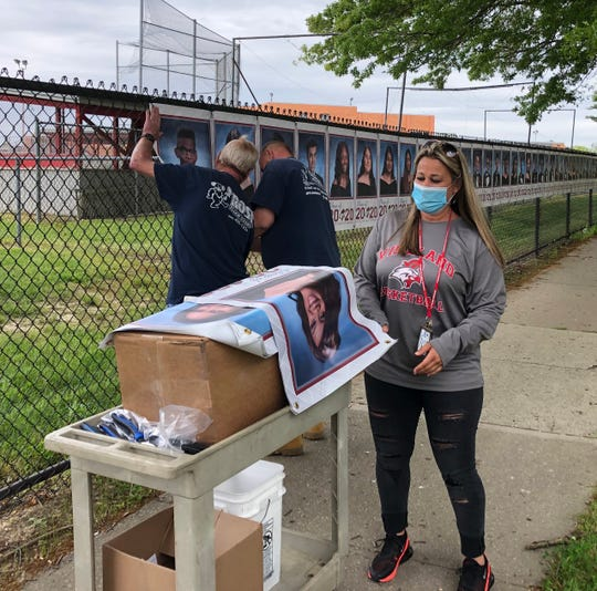 Vineland High School Assistant Principal Kim Rivera looks over VHS Class of 2020 portraits that are part of the outdoor display. Vineland Public School District staffers Jerry Capriotti (left) and John Steen, install the banners along Chestnut Avenue.