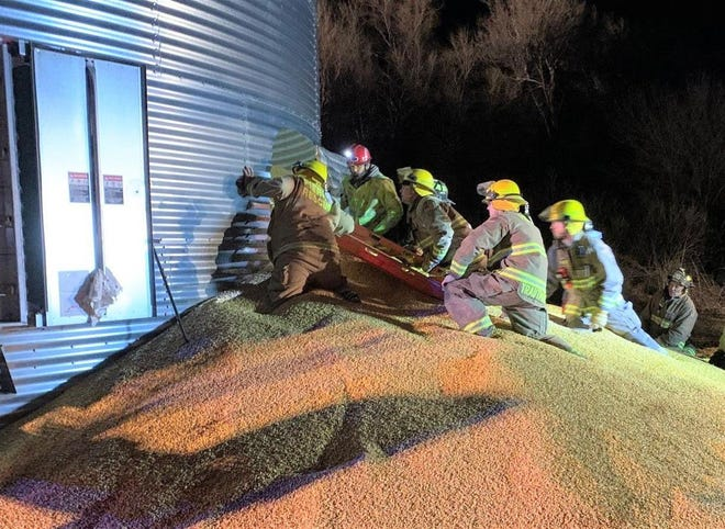 Rescue workers push a stretcher into a hole cut in a Hughes County grain bin where a man became entrapped in March. After six hours, the man was safely removed from the bin.
