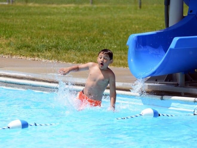 Noah Virto, a second grader at Frazeysburg Elementary, rides down the sliding board at the Frazeysburg Pool on Saturday.