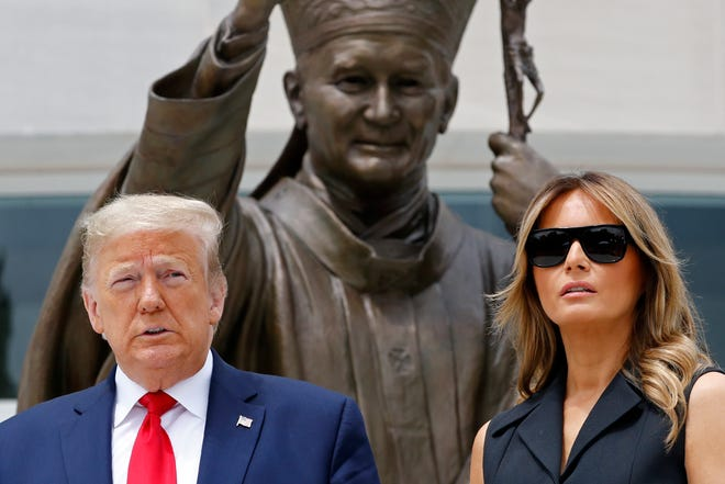 President Donald Trump and first lady Melania Trump pose before a statue of late Pope John Paul II at his shrine in Washington, June. 2, 2020.