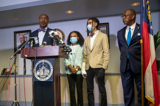 Attorney Mawuli Davis, left, speaks on behalf of Taniyah Pilgrim, center, and Messiah Young, right, during a press conference by the Fulton County District Attorney's Office in Atlanta, Monday, June 2, 2020.