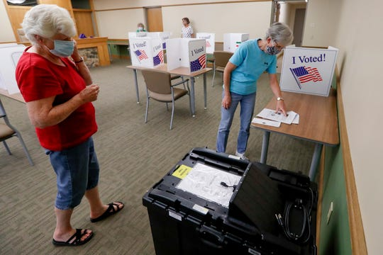 Kay Thiebaud, left, and Lynn Meyers check procedure as they start to set up one of the scanners used in tabulating the vote as they start to set up their polling place Monday, June 1, 2020, for the voting for Tuesday's Pennsylvania primary, in Jackson Township near Zelienople, Pa. (AP Photo/Keith Srakocic)
