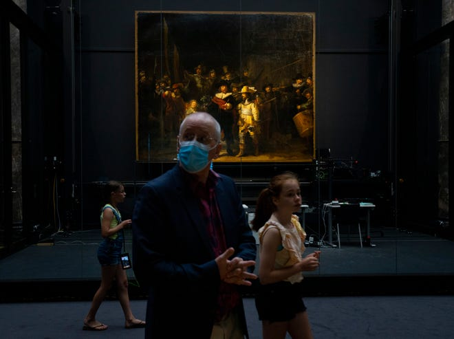 Visitors pass Rembrandt's Night Watch in the reopened Rijksmuseum in Amsterdam, Netherlands, Monday, June 1, 2020. The Dutch government took a major step to relax the coronavirus lockdown, with bars, restaurants, cinemas and museums reopening under strict conditions.