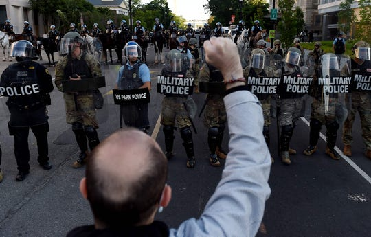 Military police members face off with demonstrators outside the White House to protest the death of George Floyd, who died in police custody in Minneapolis
