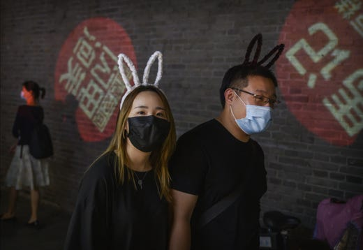 A couple wears protective masks as they walk in a commercial street while shopping on June 2, 2020 in Beijing, China.