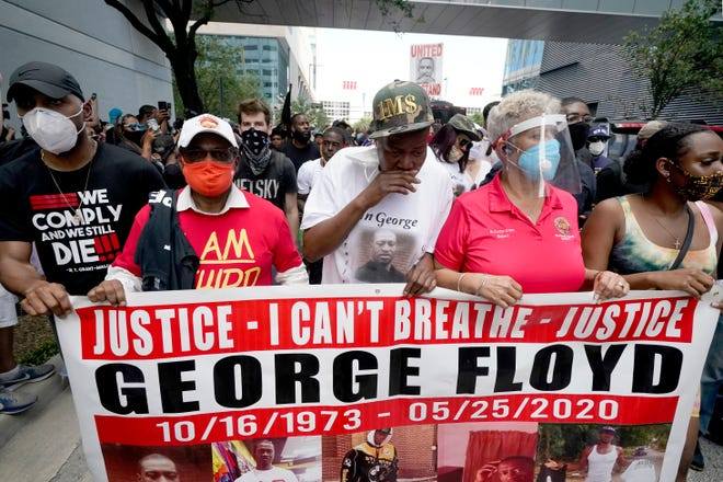 LaTonya Floyd, center, in hat, participates in a march to protest the death of her brother, George Floyd in Houston on Tuesday, June 2, 2020. Floyd died after a Minneapolis police officer pressed his knee into Floyd's neck for several minutes even after he stopped moving and pleading for air. (AP Photo/David J. Phillip)