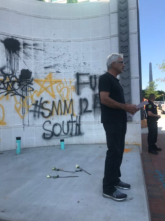 """Hotel Arras owner John McKibbon speaks to the media outside his graffiti-marked hotel June 2. McKibbon said the platform had been intended for a locally-made sculpture but that he instead would leave it as a """"testament"""" to property damage that happened during the nights of May 31 and June 1 protests."""