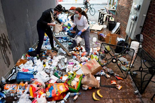 The alleyway to One World Brewing is left in disarray after Asheville Police tipped over tables of food and medical supplies June 2, 2020.
