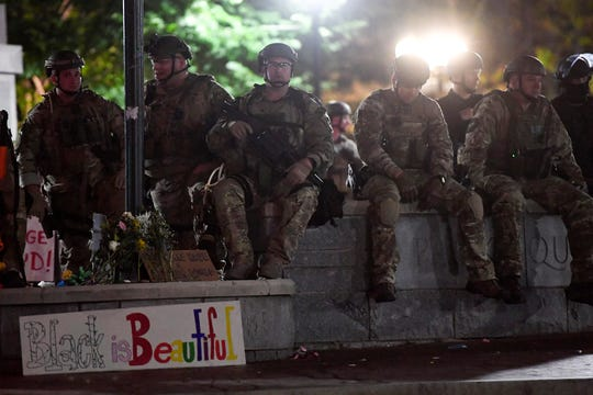 National Guard sit at Vance Monument as the night turns quiet in downtown Asheville June 2, 2020.
