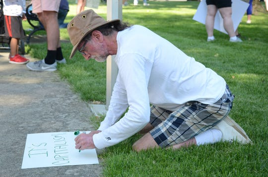 Dan Schnaitman of Fremont, Ind., and a native of Marshall, prepares a sign before the march.  Trace Christenson/The Enquirer