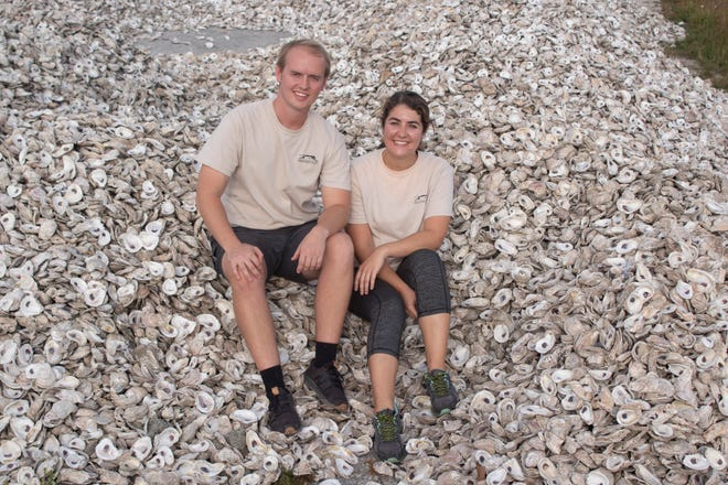 """Conservation construction lead Adam Klingenberg and conservation specialist Olivia Escandell, both with the Brevard Zoo's Restore Our Shores program, sit on a pile of oyster shells collected as part of the Shuck & Share program designed to help in """"living shoreline"""" restoration projects along the Indian River Lagoon. The program received a $39,369 Tourism + Lagoon Grant from the county for 2019-20, funded by Brevard County's 5% Tourist Development Tax on hotel rooms and other short-term rentals."""