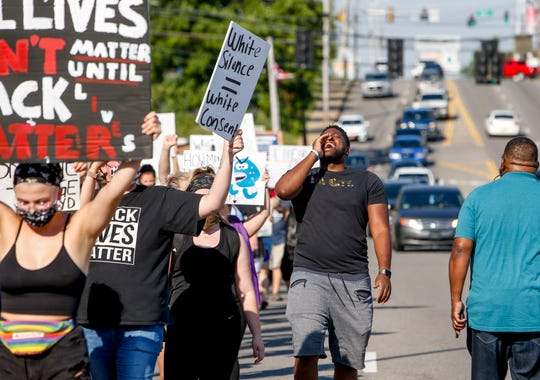 Demonstrators march down the street on their way to downtown, chanting and cheering for cars that honked as they drove by at the March Against Police Brutality along College Street in Clarksville, Tenn., on Tuesday, June 2, 2020.