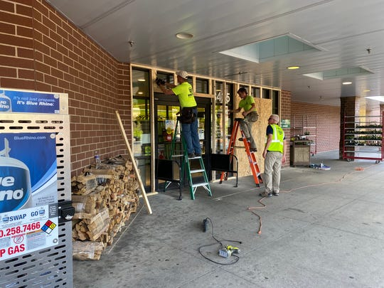 Workers board up the Price Chopper on Ingersoll Avenue in Des Moines ahead of a protest that was marching from the Sculpture Garden to Terrace Hill on June 2, 2020.