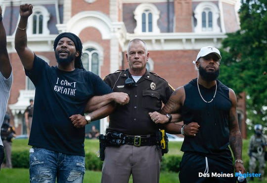 Will Robinson of Des Moines, left, and Billy Weathers, right, stand arm-in-arm with Iowa State Patrol Maj. Randy Kunert at Terrace Hill in Des Moines tonight, resulting in a peaceful conclusion to a protest at the governor's mansion.