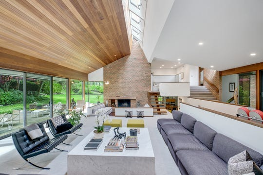 The spectacular living room has glass walls on two sides and 25 feet of skylights overhead. A second conversation group is sunken around the fireplace. Long Italian sofas are the architect's originals, just reupholstered. The wood-sheathed ceiling is a repeating theme.