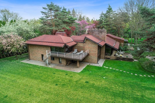 The large deck off the back of the house is part of the owner's' suite, which also has a 29-foot sleeping room and a 23-foot reading room. The stone path at right leads to the free-standing studio.