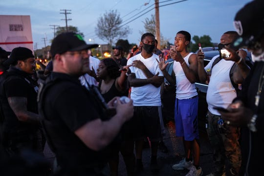 Residents talk with police after they were happy about protesters being arrested in their neighborhood on Gratiot Ave. in Detroit during the fifth day of protesting in Detroit on Tuesday, June 2, 2020.